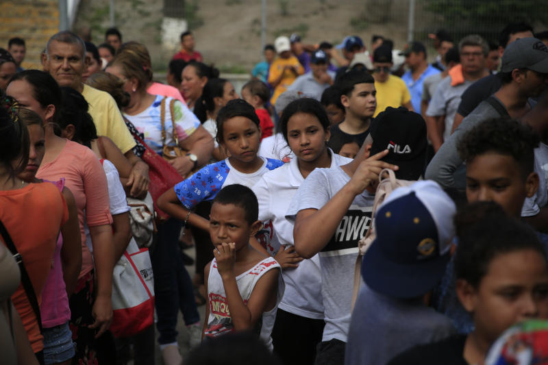 Migrants from countries including Honduras, Cuba, Venezuela, and Nicaragua, line up to receive a meal donated by volunteers from the U.S., at the foot of the bridge that crosses to Brownsville, Texas, in downtown Matamoros, Tamaulipas state, Mexico, Wednesday, June 26, 2019. Hundreds of migrants, some of whom have been in line for months, are awaiting their turn to request asylum in the U.S. (AP Photo/Rebecca Blackwell)