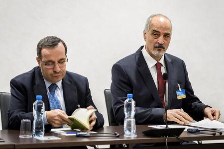Syrian ambassador to the United Nations and head of the government delegation Bashar al-Jaafari and a member of his delegation prepare notes prior to the start of a meeting with the UN Special Envoy for Syria during Intra Syria peace talks at the U.N. in Geneva, Switzerland December 14, 2017.   REUTERS/ Fabrice Coffrini/Pool