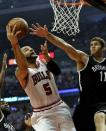 Chicago Bulls' Carlos Boozer (5) drives to the basket as Brooklyn Nets' Brook Lopez (11) defends during the first half in Game 4 of their first-round NBA basketball playoff series Saturday, April 27, 2013, in Chicago. (AP Photo/Jim Prisching)