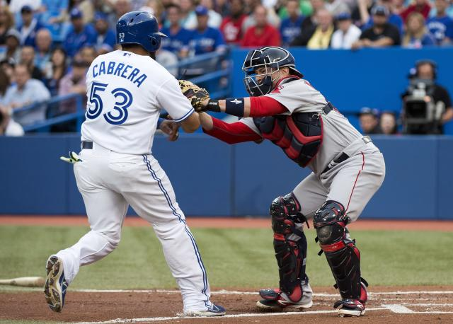Boston Red Sox catcher Christian Vazquez, right, tags out Toronto Blue Jays' Melky Cabrera (53) at home plate during first-inning baseball game action in Toronto, Wednesday, July 23, 2014. (AP Photo/The Canadian Press, Nathan Denette)