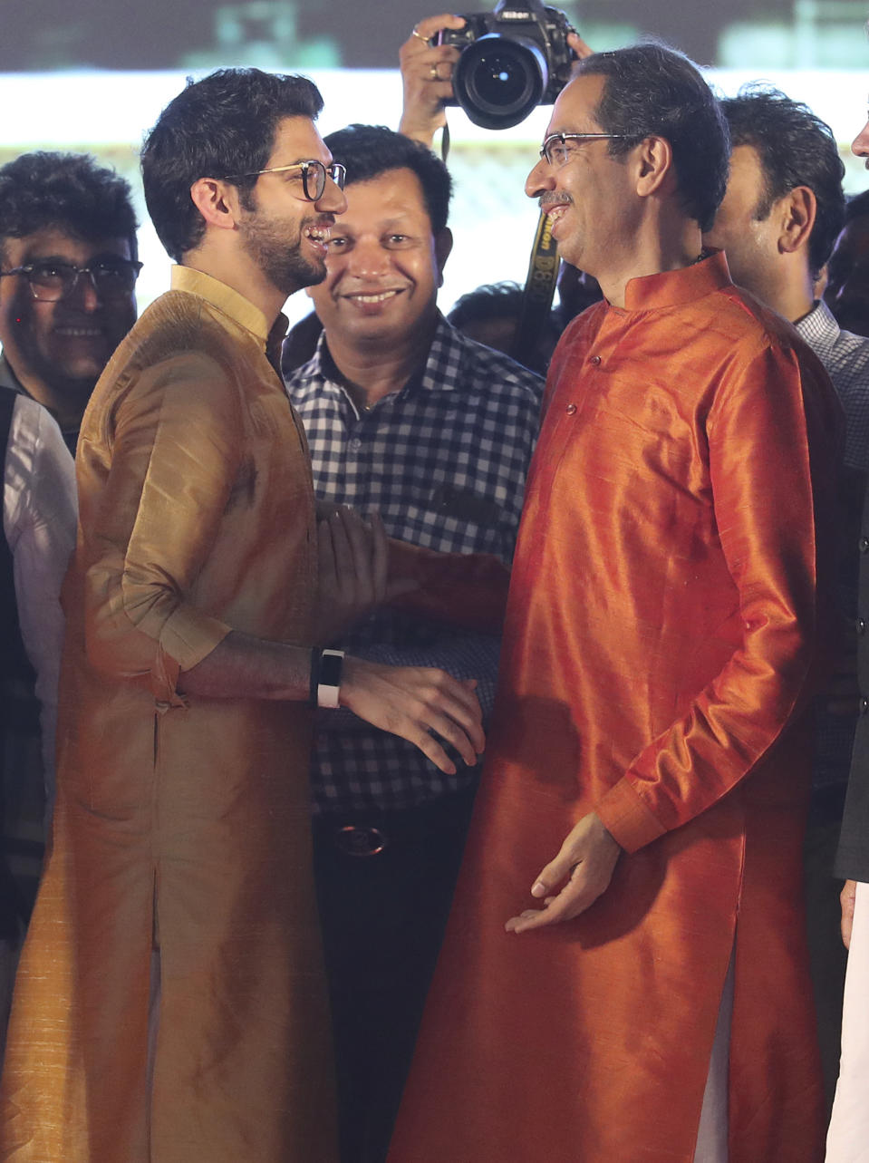 Shiv Sena party leader Uddhav Thackeray, right, is congratulated by his son Aaditya Thackeray after he took oath as chief minister of Maharashtra state during a swearing-in-ceremony in Mumbai, Thursday, Nov. 28, 2019. Supporters of the Shiv Sena, Nationalist Congress Party (NCP) and the Congress party thronged Shivaji Park to watch their leaders take oath of office. (AP Photo/Rafiq Maqbool)