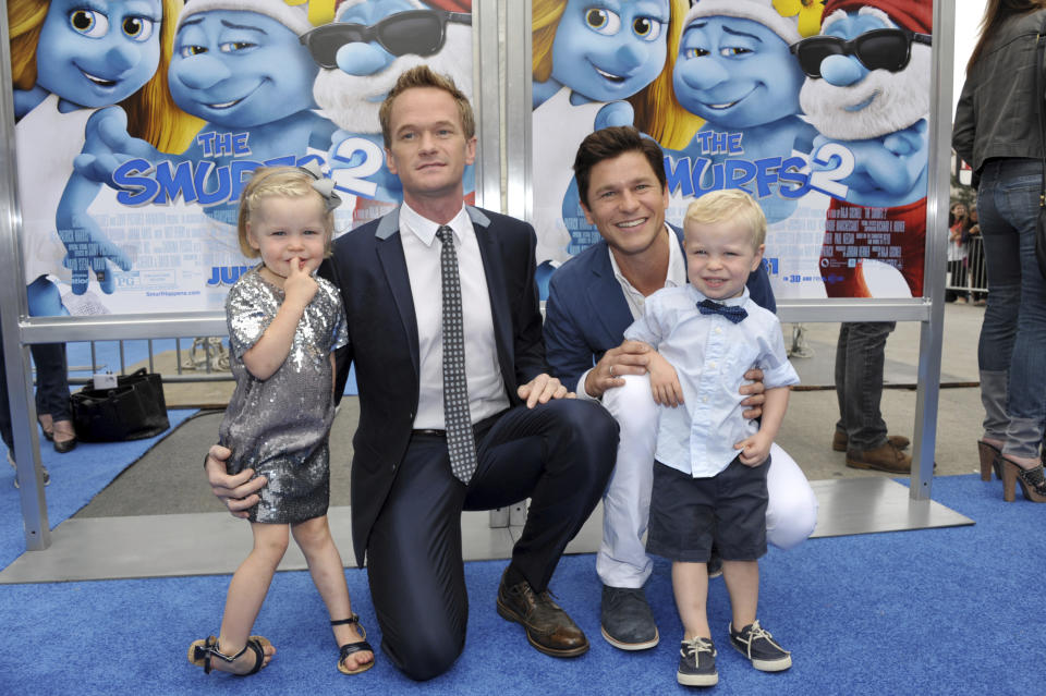 "FILE- In this July 28, 2013 file photo, celebrity couple, actor Neil Patrick Harris, center left, and chef David Burtka, center right, pose with their children, twins Harper Grace Burtka-Harris, left, and Gideon Scott Burtka-Harris, right, as they arrive to the world premiere of ""The Smurfs 2"" at the Regency Village Theatre in Los Angeles. On Saturday, Sept. 1, 2018, Harris and Burtka revive the once annual end-of-summer bash for New York's drag scene called ""Wigstock,"" at New York City's Pier 17 rooftop. The original Wigstock got its start in 1985 and was held for years on pier on Manhattan's West Side until consecutive years of rain dampened ticket revenue and bankrupted the event in 2001. (Photo by John Shearer/Invision/AP, File)"