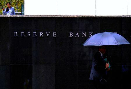 FILE PHOTO: Pedestrians walk past the Reserve Bank of Australia building in central Sydney, Australia