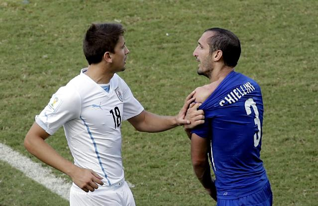 Italy's Giorgio Chiellini (3) complains after Uruguay's Luis Suarez ran into his shoulder with his teeth during the group D World Cup soccer match between Italy and Uruguay at the Arena das Dunas in Natal, Brazil, Tuesday, June 24, 2014. (AP Photo/Hassan Ammar)