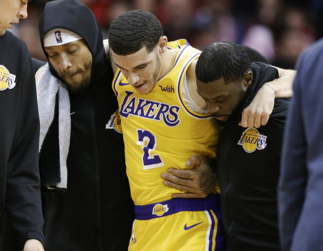 Los Angeles Lakers guard Lonzo Ball (2) is carried off the court by Michael Beasley, left, and Lance Stephenson after Ball sustained an injury during the second half of an NBA basketball game against the Houston Rockets, Saturday, Jan. 19, 2019, in Houston. (AP Photo/Eric Christian Smith)
