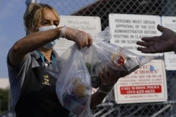 Los Angeles Unified School District food service worker Marisel Dominguez, left, distributes free school lunches on Friday, July 16, 2021, at the Liechty Middle School in Los Angeles. Flush with cash from an unexpected budget surplus, California is launching the nation's largest statewide universal free lunch program. When classrooms open for the fall term, every one of California's 6.2 million public school students will have the option to eat school meals for free, regardless of their family's income. (AP Photo/Damian Dovarganes)