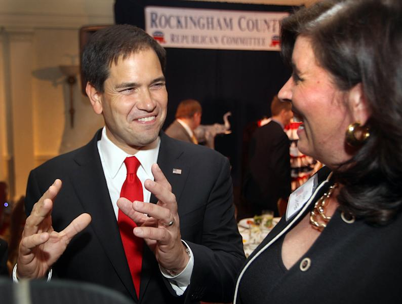 U.S. Sen. Marco Rubio, R-Fla., left, speaks with New Hampshire Republican Chairwoman Jennifer Horn at the Rockingham County Republican Committee's Freedom Founders Dinner, Friday, May 9, 2014 in New Castle, N.H. (AP Photo/Jim Cole)