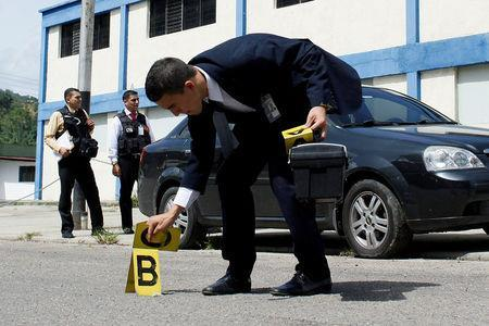 A criminal investigator collects evidence in the area where a woman was shot when looters raided state food warehouses, in San Cristobal, Venezuela, June 6, 2016. REUTERS/Carlos Eduardo Ramirez