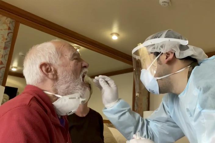 Paul Molesky, left, gets a DNA swab test in his cabin room on the Diamond Princess (AP)
