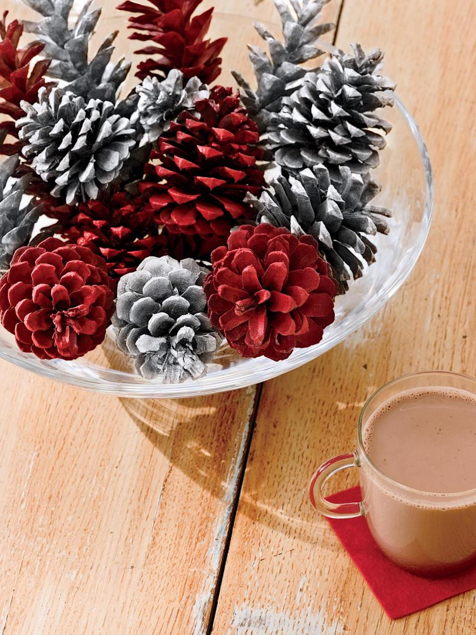 """<p>Here's a fast, festive way to spruce up some evergreen seeds: Lightly spray-paint half the cones in cheery cranberry, the rest in shimmery silver; display in a clear glass bowl. Or to make a pop art-y piece, coat cones completely in a bright lime or gold.</p><p><a class=""""link rapid-noclick-resp"""" href=""""https://www.amazon.com/12-Ponderosa-Decorative-UNSCENTED-Displays/dp/B016YWC15Y/?tag=syn-yahoo-20&ascsubtag=%5Bartid%7C10055.g.2196%5Bsrc%7Cyahoo-us"""" rel=""""nofollow noopener"""" target=""""_blank"""" data-ylk=""""slk:SHOP PINECONES"""">SHOP PINECONES</a></p>"""