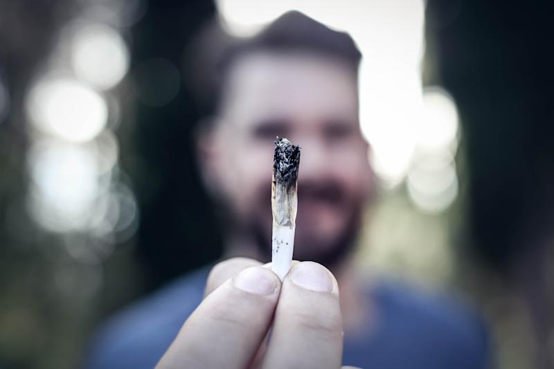 A bearded man holding a lit cannabis joint in his outstretched fingertips.