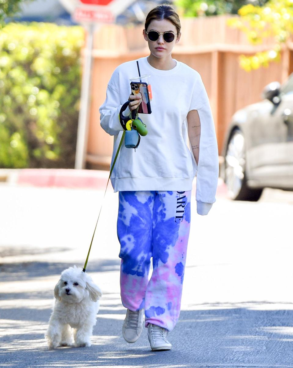 <p>Lucy Hale wears a white top and tie-dye bottoms while out on a walk with her dog in Studio City on Wednesday.</p>