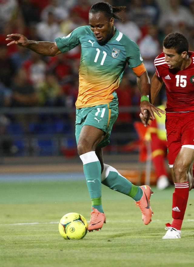 FILE - In this June 9, 2012, file photo, Ivory Coast's Didier Drogba, left, challenges for the ball with Morocco's Benlamalem Ismail, right, during their World Cup qualifying match between Ivory Coast and Morocco, in Marrakech, Morocco. Captain and national idol Didier Drogba remains at the center of the country's hopes despite turning 36 last month. (AP Photo/Abdeljalil Bounhar, File)