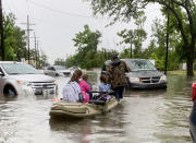 Parents use boats to pick up students from schools after nearly a foot of rain fell in Lake Charles, La., Monday, May 17, 2021. (Rick Hickman/American Press via AP)