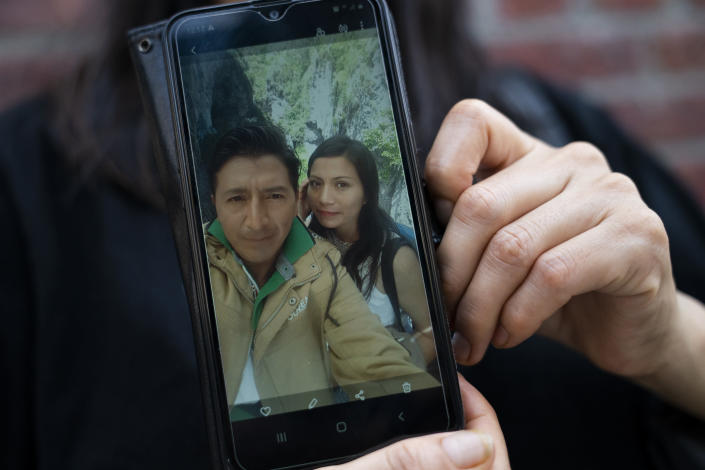 Monica Muquinche holds a picture of herself with her husband Carlos Lopez in her neighborhood in the Brooklyn borough of New York, Thursday, Aug. 26, 2021. Muquinche, whose husband disappeared in 2020 while trying to reach the U.S., is part of an extraordinary wave of Ecuadorians coming in the United States. (AP Photo/John Minchillo)