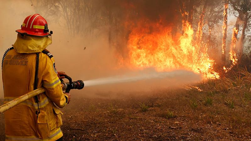 Picture of a fire fighter battling a blaze along Old Bar road in Old Bar, NSW, Saturday, November 9, 2019.