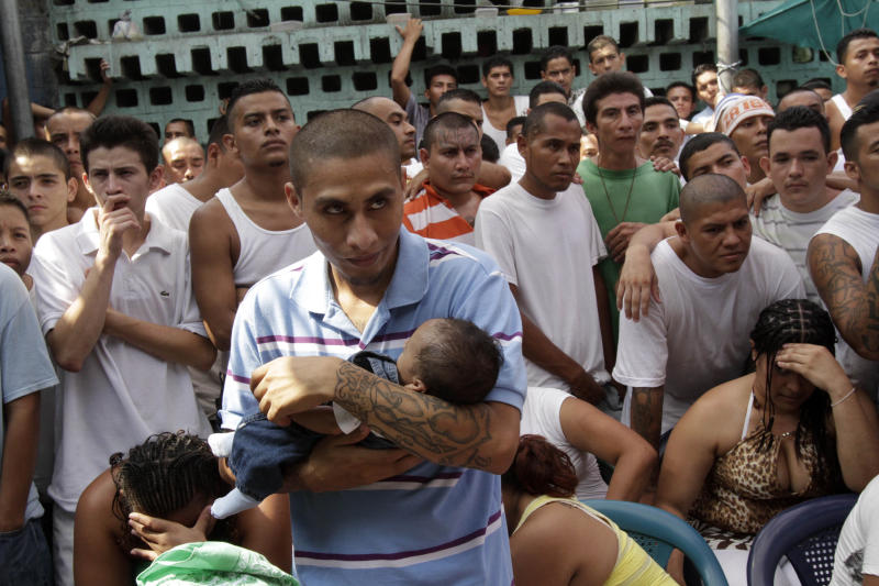 In this May 2, 2012 photo, an inmate belonging to the M-18 gang holds his child during family visit time inside the prison in Quezaltepeque, El Salvador. Six months after El Salvador brokered an historic truce between two rival gangs to curb the nation's daunting homicide rate, officials are split over whether the truce actually works. The gangs, which also operate in Guatemala and Honduras, are seeking truce talks in those countries as well. ( AP Photo/Luis Romero)