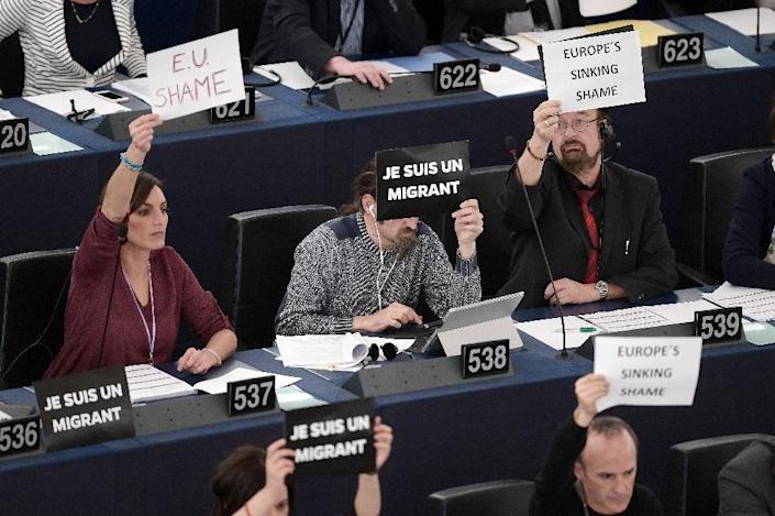 """Members of the EU parliament hold up signs reading """"Je suis un migrant"""" (C) (""""I am a migrant"""") at the European Parliament in Strasbourg, on April 29, 2015 (AFP Photo/Frederick Florin)"""