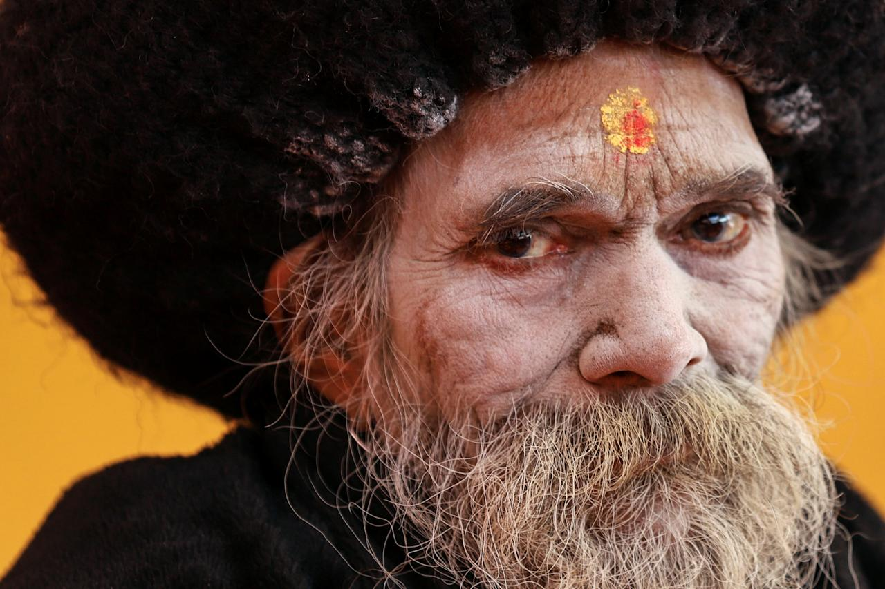 """<p>A Sadhu or a Hindu holy man watches a religious ceremony ahead of the """"Kumbh Mela"""", or the Pitcher Festival, in Prayagraj, previously known as Allahabad, India, January 8, 2019. REUTERS/Jitendra Prakash TPX IMAGES OF THE DAY </p>"""