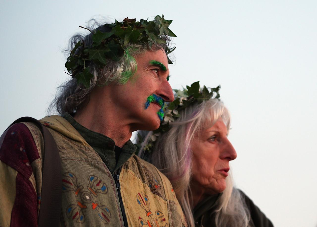 GLASTONBURY, ENGLAND - MAY 01:  A couple watch the sun rise as they join in a Beltane dawn celebration service in front of St. Michael's Tower on Glastonbury Tor on May 1, 2013 in Glastonbury, England. Although more synonymous with International Workers' Day, or Labour Day, May Day or Beltane is celebrated by druids and pagans as the beginning of summer and the chance to celebrate the coming of the season of warmth and light. Other traditional English May Day rites and celebrations include Morris dancing and the crowning of a May Queen with celebrations involving a Maypole.  (Photo by Matt Cardy/Getty Images)