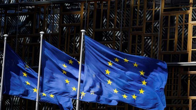 A picture taken on May 28, 2020 in Brussels shows the European Union flags fluttering in the aire outside the European Commission building in Brussels