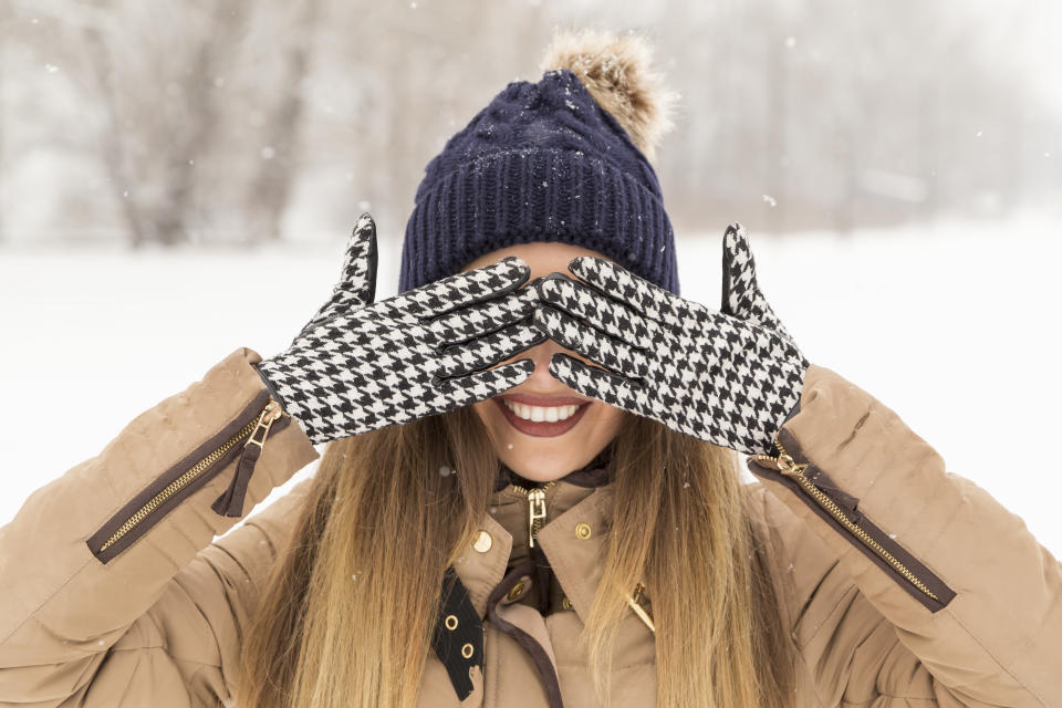 Woman wearing warm winter clothes, hiding her eyes with hands in gloves,
