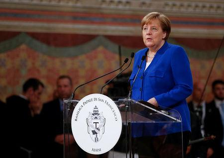 """German Chancellor Angela Merkel speaks after she received a """"Peace Lamp"""" award from the Catholic monks at the Basilica of St. Francis in Assisi"""