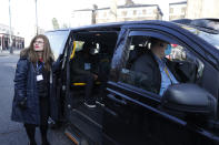 Dr Sharon Raymond with one of the London Taxi cabs being used as a Vaxi Taxi during the pilot project of pop up vaccination drive 'Vaxi Taxi' in Kilburn, London, Sunday, Feb. 28, 2021. The pilot scheme, funded by the Covid Crisis Rescue Foundation, aims to help ferry supplies and patients to temporary clinics set up in faith and community centres across the capital. People don't even need to leave the backseat if they didn't want to in order to receive their inoculation. (AP Photo/Alastair Grant)
