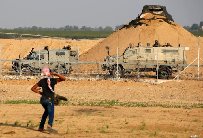 A Palestinian protester throws a rock at Israeli soldiers during a demonstration along the barrier between Israel and the Gaza Strip on November 9, 2018 (AFP Photo/Said KHATIB)
