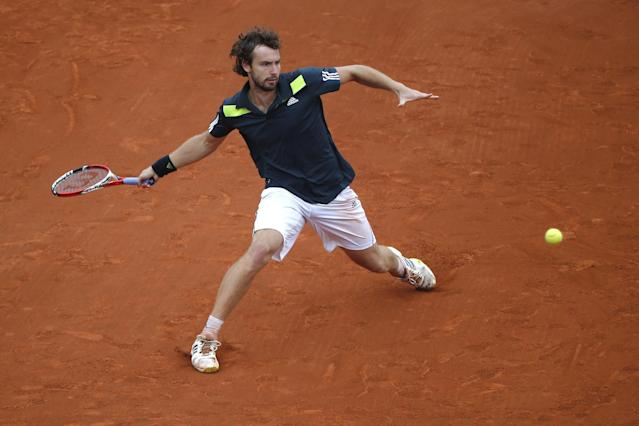 Latvia's Ernests Gulbis returns the ball during the fourth round match of the French Open tennis tournament against Switzerland's Roger Federer at the Roland Garros stadium, in Paris, France, Sunday, June 1, 2014. (AP Photo/Michel Euler)