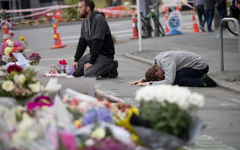 Mourners pray near the Linwood mosque in Christchurch, New Zealand - AP
