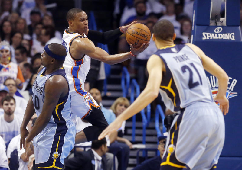 Oklahoma City Thunder guard Russell Westbrook, second from left, passes between Memphis Grizzlies forward Zach Randolph (50) and forward Tayshaun Prince (21) in the second quarter of Game 5 of an opening-round NBA basketball playoff series in Oklahoma City, Tuesday, April 29, 2014. (AP Photo)