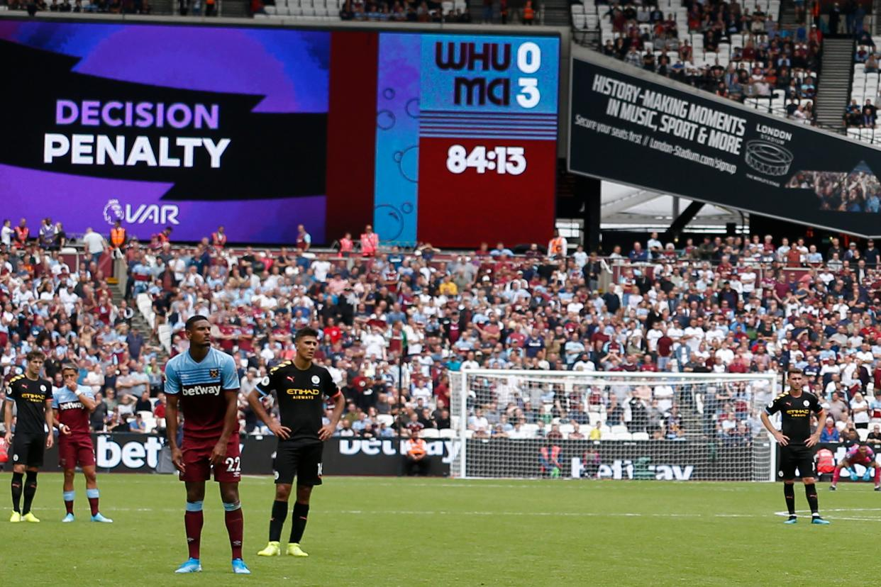 The big screen displays the VAR decision ruling that a Manchester City penalty, that on the first attempt was saved, must be retaken during the English Premier League football match between West Ham United and Manchester City at The London Stadium, in east London on August 10, 2019. (Photo by Ian KINGTON / AFP) / RESTRICTED TO EDITORIAL USE. No use with unauthorized audio, video, data, fixture lists, club/league logos or 'live' services. Online in-match use limited to 120 images. An additional 40 images may be used in extra time. No video emulation. Social media in-match use limited to 120 images. An additional 40 images may be used in extra time. No use in betting publications, games or single club/league/player publications. /         (Photo credit should read IAN KINGTON/AFP/Getty Images)