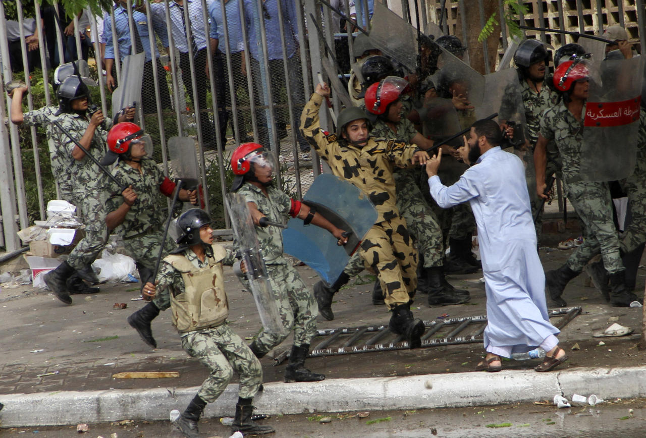 Egyptian soldiers raise their batons at a protester during clashes outside the Ministry of Defense in Cairo, Egypt, Friday, May 4, 2012. Egyptian armed forces and protesters clashed in Cairo on Friday, with troops firing water cannons and tear gas at demonstrators who threw stones as they tried to march on the Defense Ministry, a flashpoint for a new cycle of violence only weeks ahead of presidential elections. (AP Photo/Ahmed Gomaa)