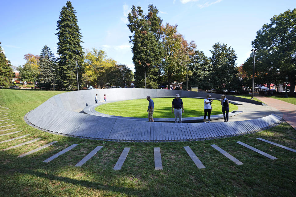 Visitors look over inscriptions on the walls of the Memorial to Enslaved Laborers at the University of Virginia in Charlottesville, Va., Friday Oct. 23, 2020. Devon Henry's company, Team Henry Enterprises, was the general contractor for the recently completed Memorial that honors the enslaved people who built and sustained the Thomas Jefferson-founded university. (AP Photo/Steve Helber)