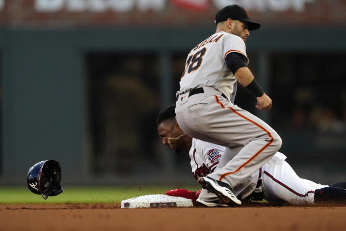 Atlanta Braves' Ozzie Albies beats the throw to San Francisco Giants second baseman Tommy La Stella (18) as he steals second base during the first inning of a baseball game Saturday, Aug. 28, 2021, in Atlanta. (AP Photo/John Bazemore)