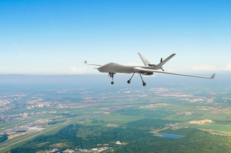 A military drone flying at low altitude over green fields