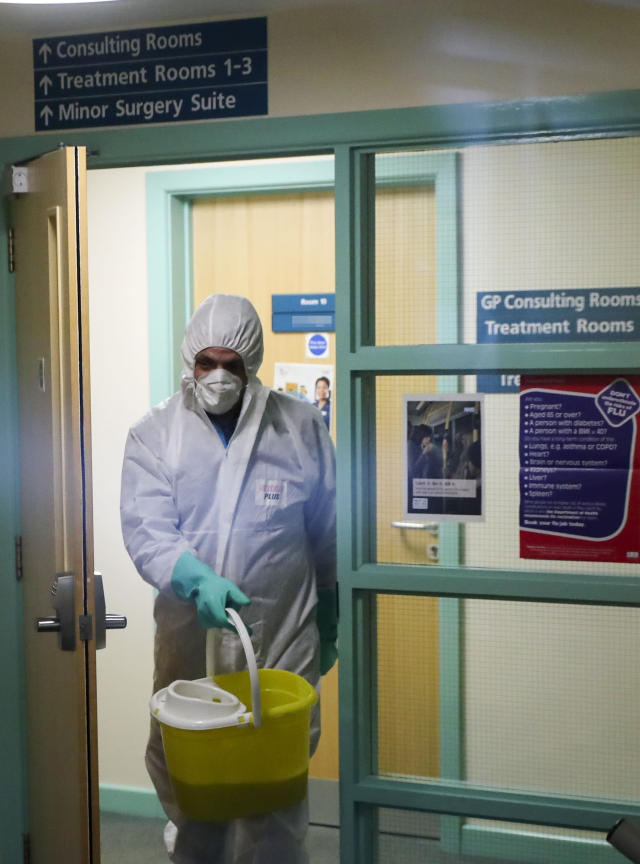A man in protective clothing cleans the County Oak Medical Centre GP practice in Brighton (PA Images)