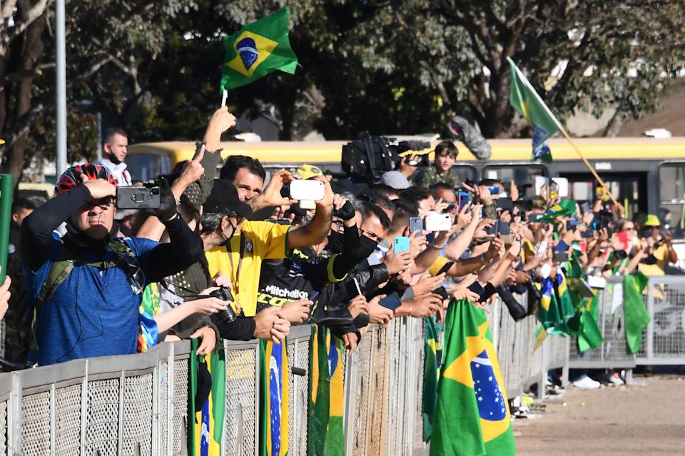 Supporters of Brazilian President Jair Bolsonaro attend a military vehicles parade in front of the Planalto Palace in Brasilia, on August 10, 2021. - Bolsonaro is accused of using the armed forces for a show of force to intimidate National Congress, where a bill is being debated to modify the electronic voting system. (Photo by EVARISTO SA / AFP) (Photo by EVARISTO SA/AFP via Getty Images)