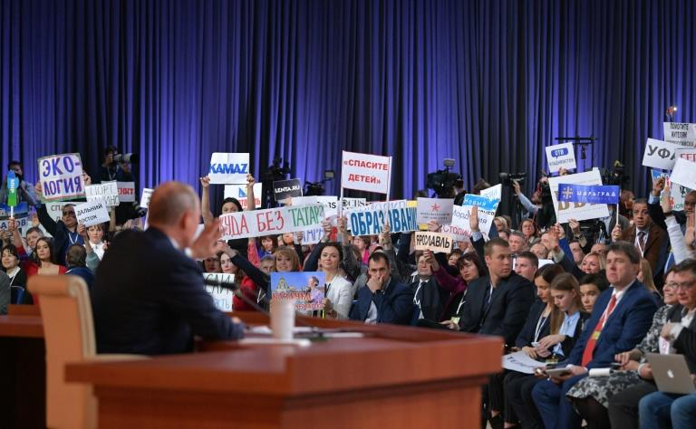 Journalists hold up signs to indicate the nature of their question at Putin's press conference