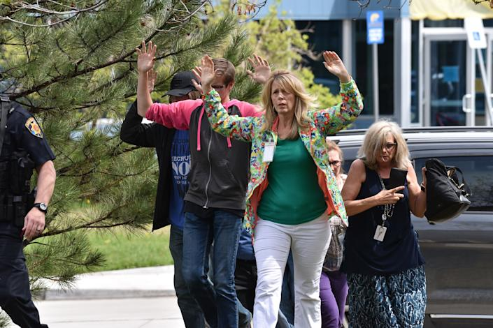 Students and teachers raise their arms as they exit the scene of a shooting in Highlands Ranch, Colorado, on May 7 , 2019..