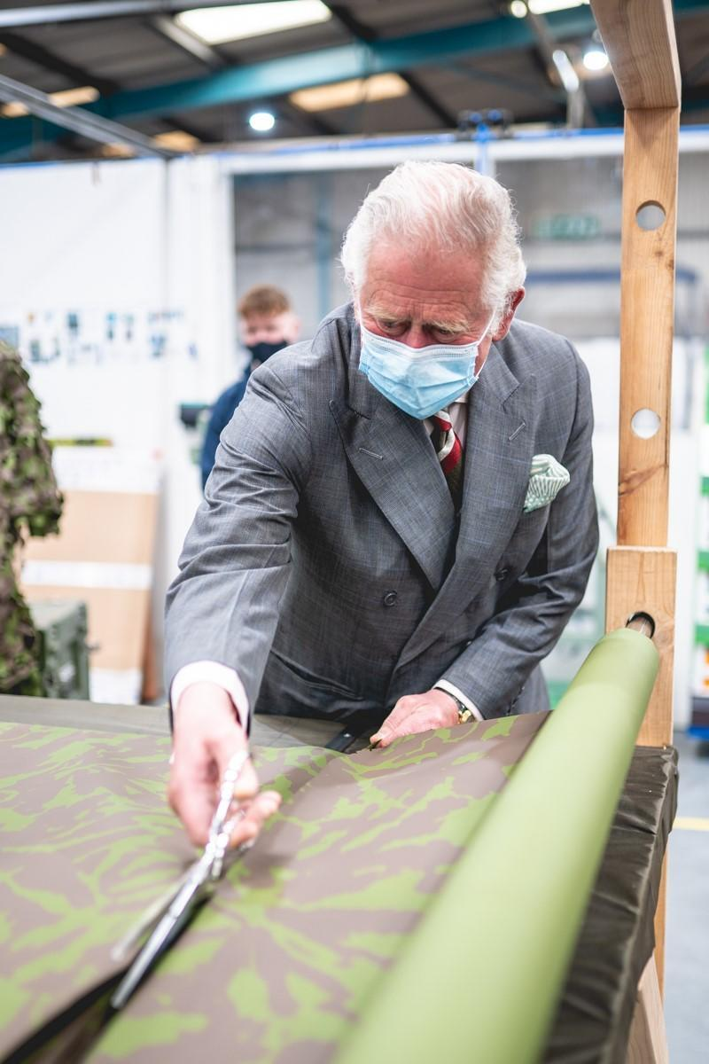 Charles cuts camouflage netting during his visit