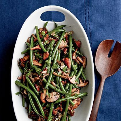 """<p>Exotic <a href=""""https://www.myrecipes.com/t/vegetables/mushrooms"""" rel=""""nofollow noopener"""" target=""""_blank"""" data-ylk=""""slk:mushrooms"""" class=""""link rapid-noclick-resp"""">mushrooms</a>, butter, and a splash of sherry add a punch of flavor to these humble haricots verts. </p>"""