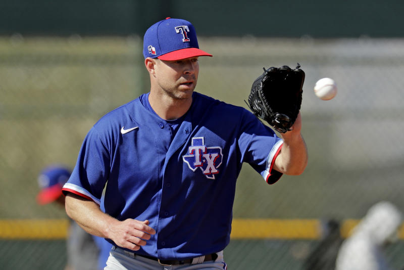 Texas Rangers pitcher Corey Kluber participates in a drill during spring training baseball practice Friday, Feb. 14, 2020, in Surprise, Ariz. (AP Photo/Charlie Riedel)