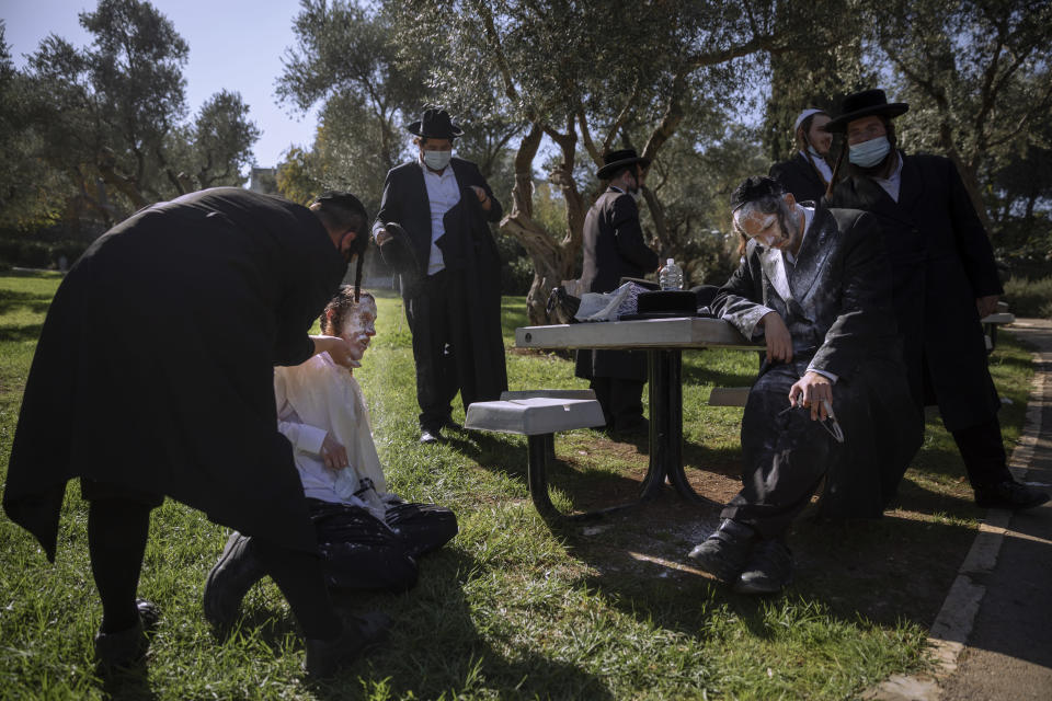 Ultra-Orthodox Jewish men are covered with flour after being pepper sprayed by security guards during a protest against the construction of a hotel at a site that protesters claim contains ancient graves, in Jerusalem, Wednesday, Nov. 18, 2020. (AP Photo/Oded Balilty)