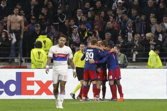 Lyon's Memphis Depay, left, reacts after CSKA's Ahmed Musa scored a goal and celebrate with teammates during the Europa League, round of 16 second leg soccer match between Lyon and CSKA Moscow in Decines, near Lyon, central France, Thursday March 15, 2018. (AP Photo/Laurent Cipriani)