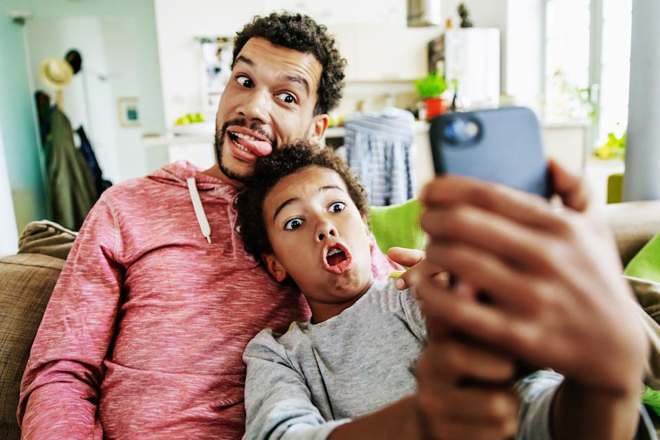 A father and son at home pulling silly faces while taking a selfie together on a smartphone.