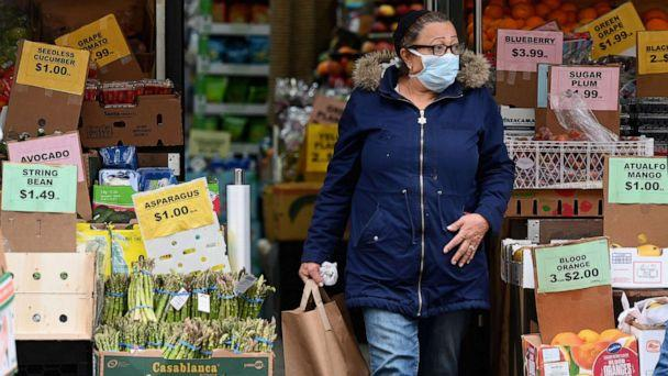 PHOTO: A customer wearing a facemask leaves with groceries from a local supermarket on March 20, 2020, in the Brooklyn borough of New York. (Angela Weiss/AFP via Getty Images)
