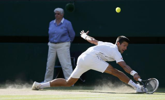 Novak Djokovic of Serbia hits a return against Roger Federer of Switzerland during their men's singles finals tennis match on Centre Court at the Wimbledon Tennis Championships in London July 6, 2014. REUTERS/Stefan Wermuth (BRITAIN - Tags: SPORT TENNIS)