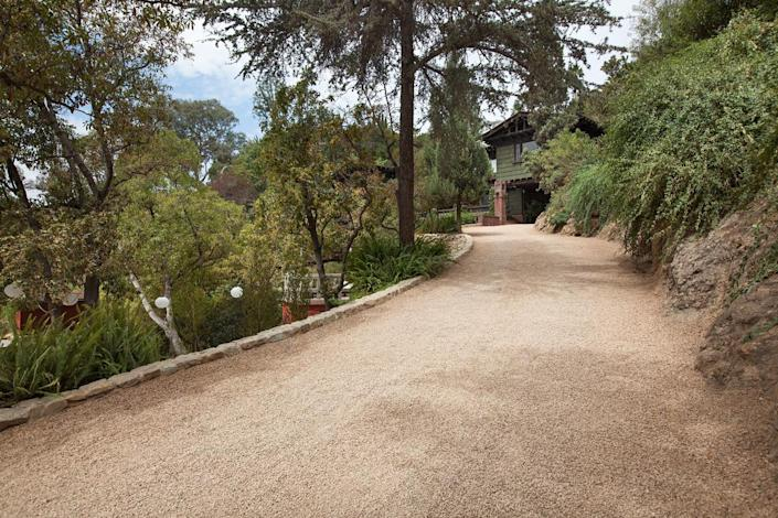 <p>There's more to this driveway than meets the eye. Fenton had the black asphalt covered with gravel, so people would feel more like they were visiting a country estate.</p>